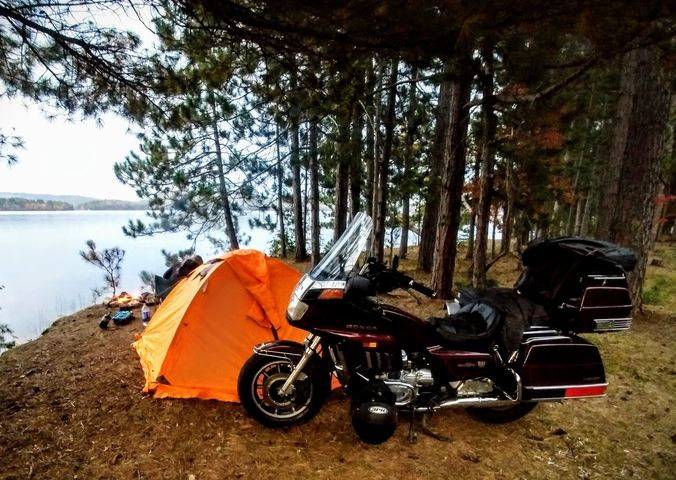 Motorcycle and tent by lake