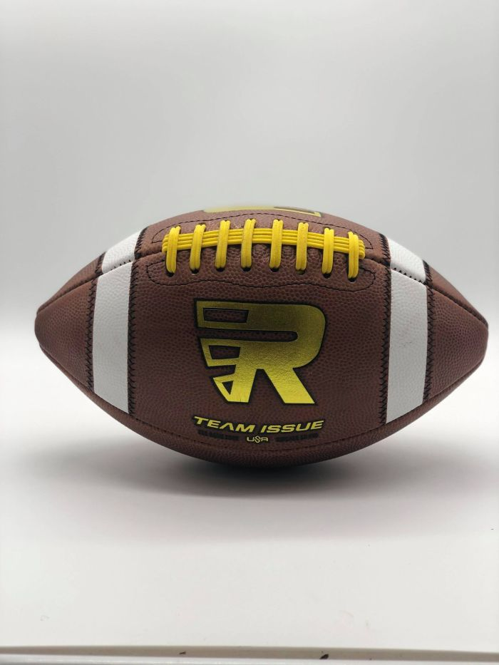 Leather american game ball with gold R logo and yellow lace in photobooth