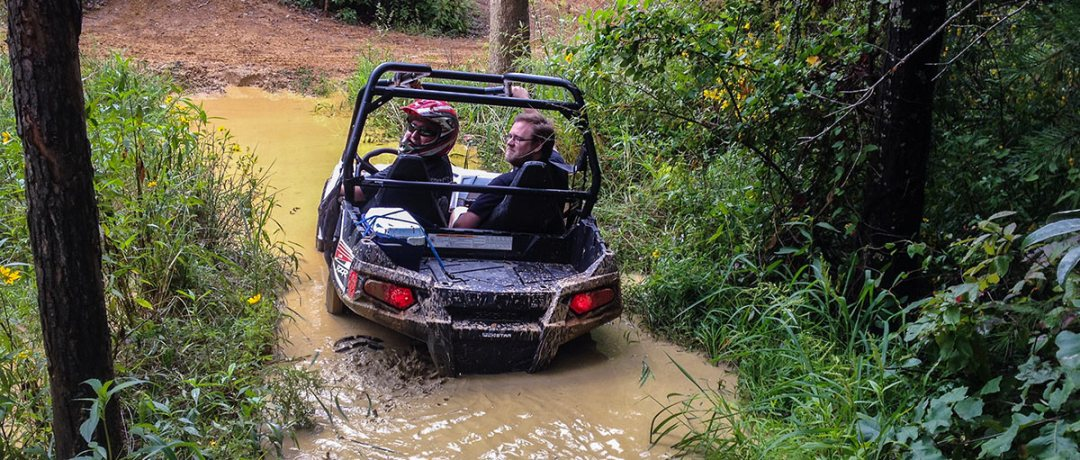 ATV riders going through a creek at the trails
