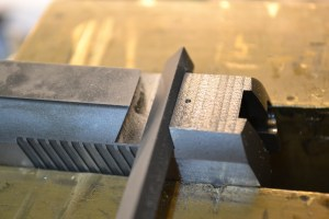A 65 degree file is used to fit the rear sight.  This file has two safe edges (no teeth) and one face that cuts.  This keeps the file from removing material where you don't want it too.