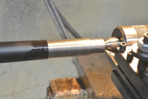 I like to turn the tenon and threads for Surefire brakes between centers. I mount the barrel tenon in a four-jaw chuck and use a 60 degree center drill to run a counterbore in the muzzle end to allow the live center to be firmly placed in the barrel.