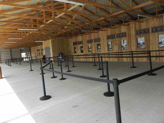 This image shows a completely empty line queue at the entrance of the Ark Encounter exhibit. The line queue is under a metal roof with wooden beams supporting it. The line queue is made up of movable plastic posts with expandable fabric partitioners, and a row of ticket booths are behind the line queue. The ticket booths are also empty.