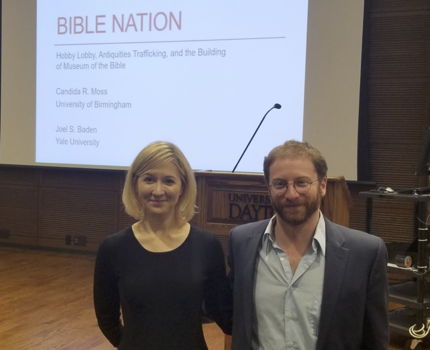 This image shows Candida Moss and Joel Baden in the foreground and a projector screen of the title of their book, Bible Nation, in the background.