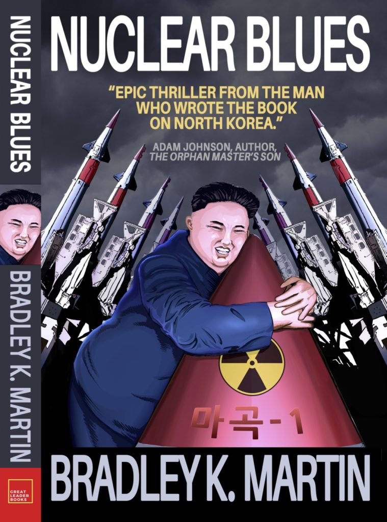 This book cover for the novel Nuclear Blues shows the North Korean leader Kim Jong-un embracing a red nuclear bomb. On either side of Kim Jong-un, missiles are lined up to launch.