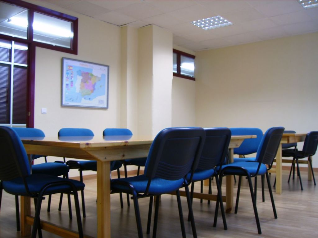 This image shows a classroom in which empty blue chairs surround a long wooden table. A map hangs in the background.