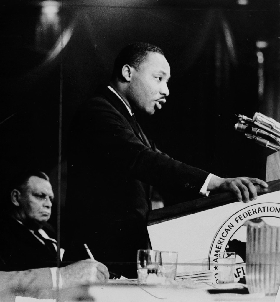 This is a black and white image of Dr. Martin Luther King, Jr. from a side view. He is standing at a podium, speaking. His hands are resting on the podium. In the background, a man listens to Dr. King. In the foreground, we see a hand of someone writing notes, and a few water glasses and water pitcher on a table.