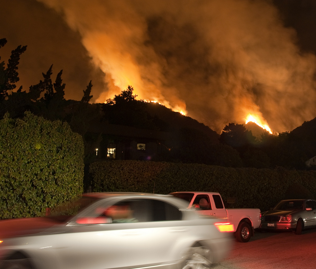This image shows the 2018 California wildfires at night. The fires appear in the background while a gray car drives by in the foreground. A White truck and another car are parked on the street as the fires approach a house in the distance.