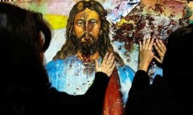 Jesus painting splattered with the blood of Christian worshipers killed during the 2011 bombing of the Church of Two Saints