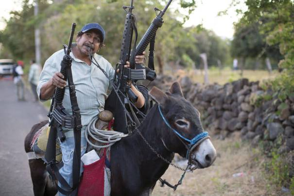 4 el-fin-de-las-autodefensas Mexican militant riding a donkey and holding his guns