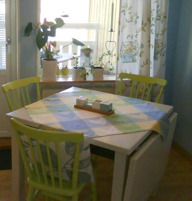 Matplatsen i köket. Utgång till balkong strax till vänster i bild. Bordet är ombyggt från ett långbord till kvadrat, och målat. Gamla stolar som målats i lime.