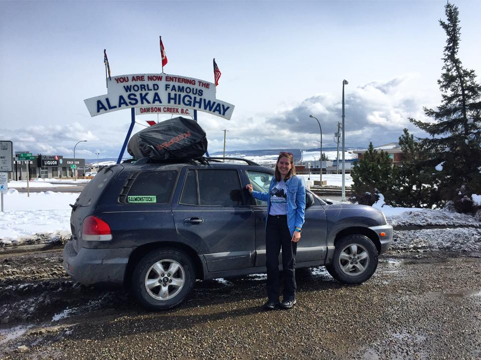Riley poses with her car at the signpost at the beginning of the Alaska Highway