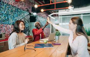 happy diverse female coworkers giving high five after successful deal