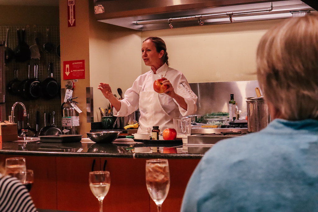 Should bloggers and influencers charge a day rate or an event fee?|Chef holding an apple at a cooking demo