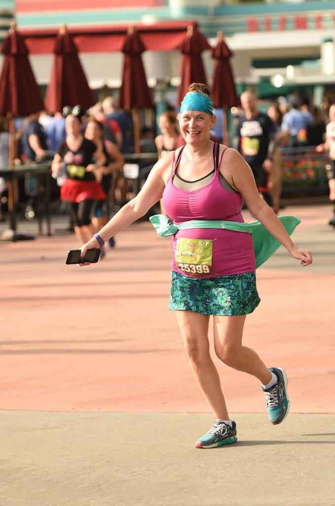 Disney Wine and Dine Half Marathon Weekend - Your Questions Answered|Run Disney Ripped Jeans and Bifocals Smiling woman running in purple top and green skirt