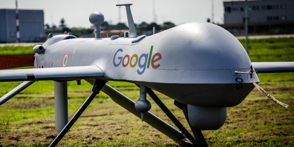 Drone with writing saying Google on it in a field with green grass and buildings in the background.