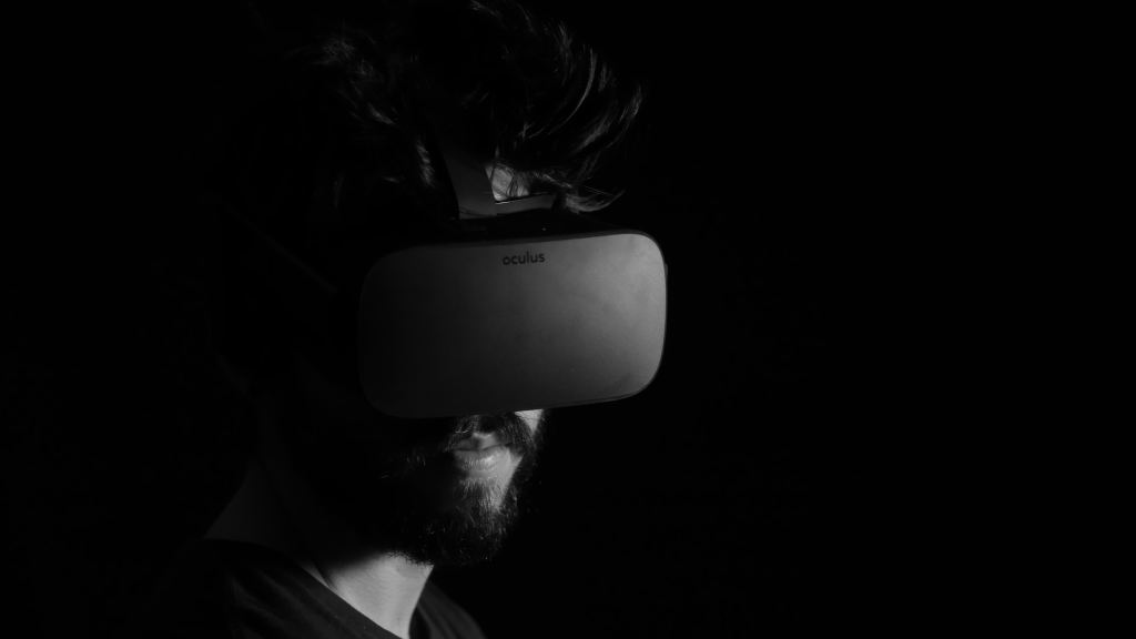 Black and white photo of bearded man from neck up wearing an Oculus Rift over his eyes.