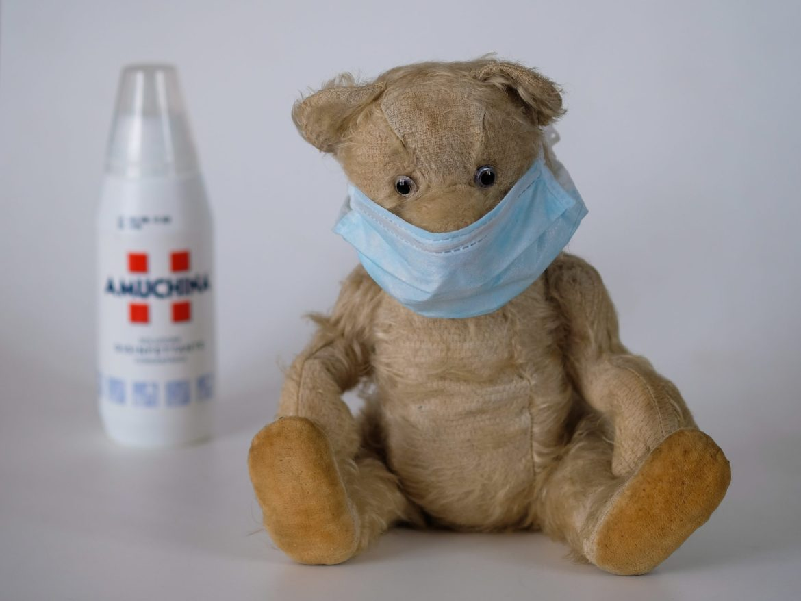 Teddy bear wearing a surgical mask in the foreground with a bottle of disinfectant in the background