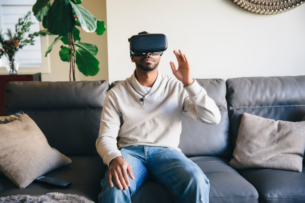man wearing a VR headset seated on couch