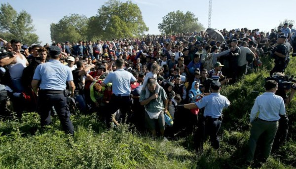Policemen direct migrants during a stampede to board a bus in Tovarnik, Croatia September 17, 2015.  REUTERS/Antonio Bronic