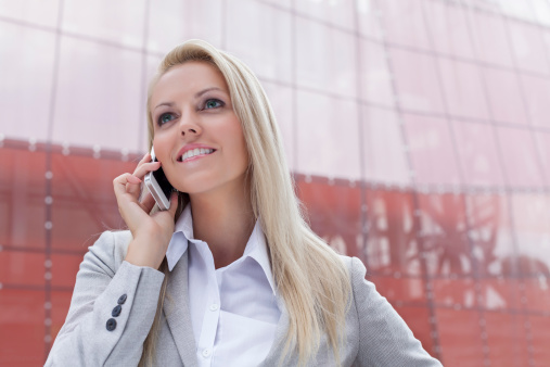 Happy young businesswoman communicating on smart phone against office building