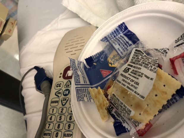 An off-center photo of a hospital bed, with a call device and a paper plate with saltine crackers.