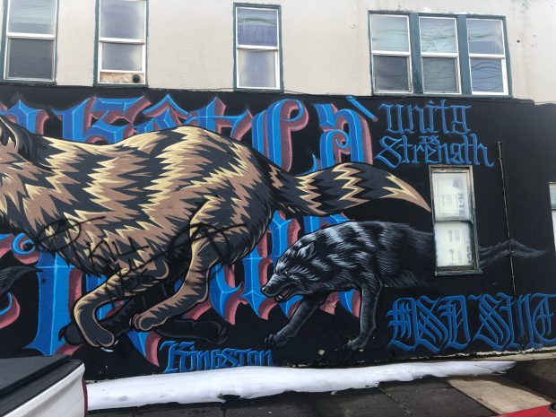 Mural painted on side of wall with fierce looking wolves, Germanic lettering, some reading: Unity Is Strength