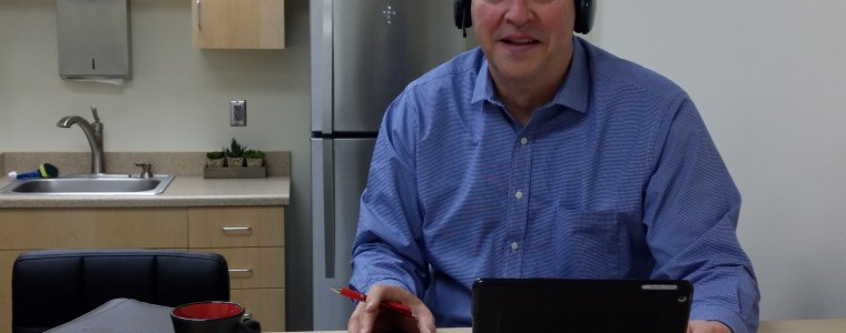 man working remotely with headset in living space