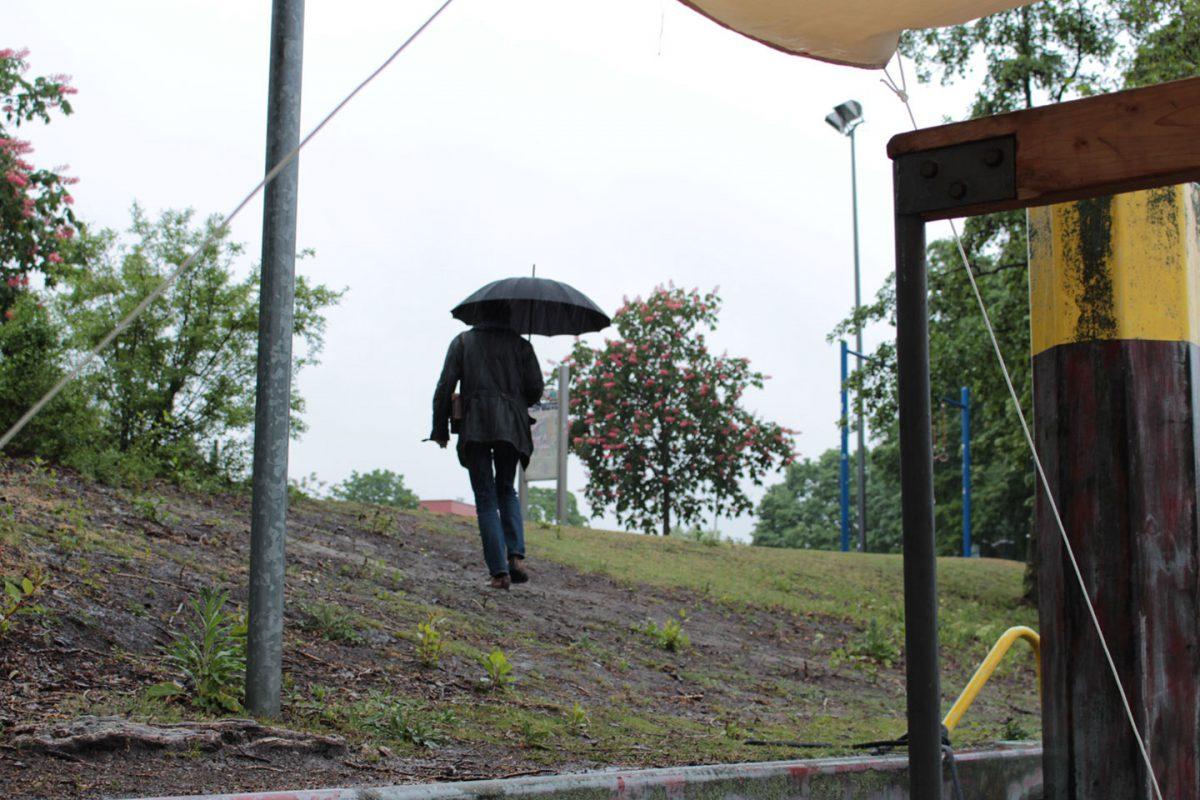 Peter von hinten mit Regenschirm wie er das Ufer hinaufgeht.