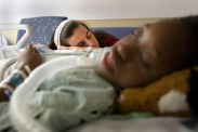 Chaney Roko sleeps over her sedated adopted daughter, Mary Roko, 9, inside the Intensive Care Unit of the Strong Memorial Hospital on Monday, Sept. 14, 2015 in Rochester, N.Y. Mary, who suffers from scoliosis was given morphine after having back surgery that would correct her spine.