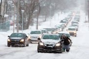 Megan Potyczka, right, and others help push a car up N. Kendall Ave. Tuesday, March 1, 2016 in Kalamazoo, Mich. A winter snowstorm caused delays in Kalamazoo.