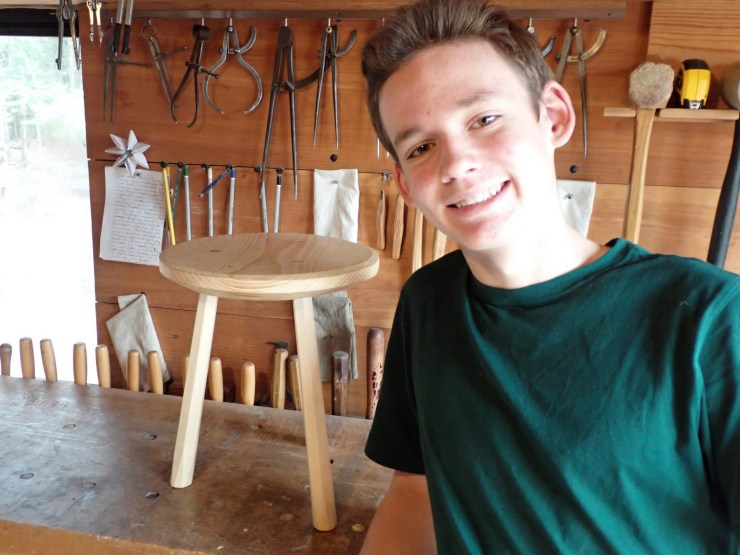 Asher stands next to his three-legged staked stool in the workshop at RivenJoiner.com.