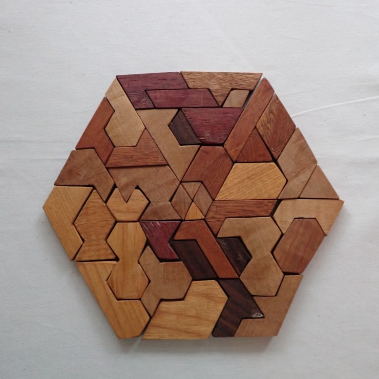 A hexagon wooden puzzle, hand-carved by Spencer Michalski at RivenJoiner.com.