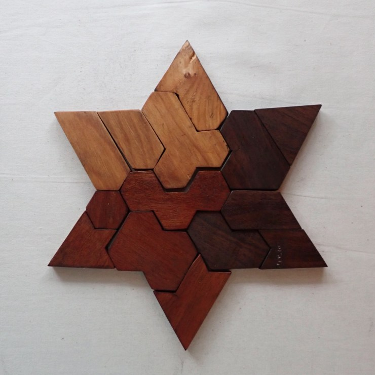 A star-shaped wooden puzzle, hand-carved by Spencer Michalski at RivenJoiner.com.