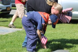 Kaden Linnen, 7,  places a flag with his dad Brian Linnen