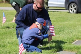 Julien Micheels, 6, places a flag with his dad Larry Micheels.