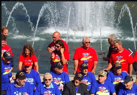 Honor Flight veterans and their guardians in front of the World War II memorial fountain.