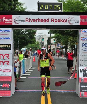BILL LANDON PHOTO   Riverhead Rocks triathlon winner Tim Steiskal of Brookhaven as he crosses the finish line.