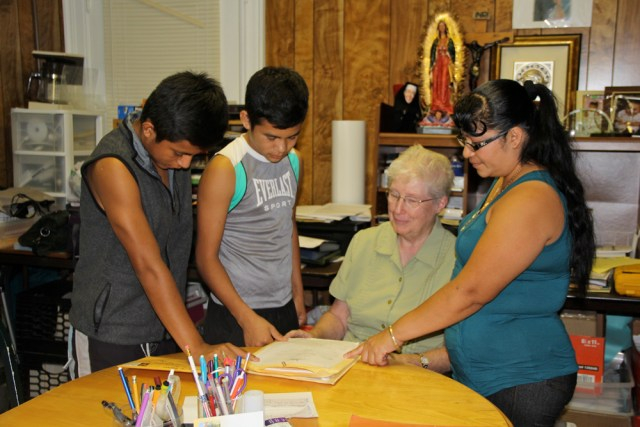 Sister Margaret Smyth of the North Fork Spanish Apostolate (center) with Estabon, 16, and Pedro, 14, and their mother Marta Tuesday afternoon. (Credit: Carrie Miller)