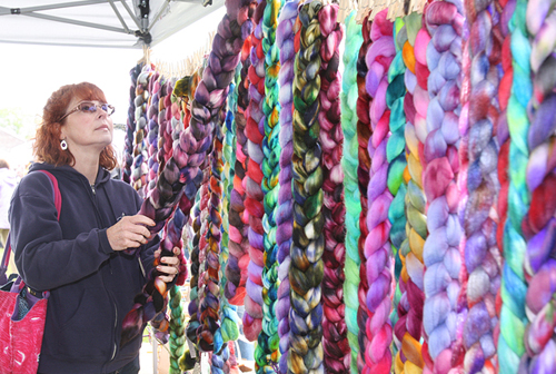 Linda Romar of Maryland looks at the Marino sheep rovings hand dyed by 'indy dyer fiber artist' Charisse DeCarlo of Lake Grove in 2012. (Credit: Barbaraellen Koch, file)