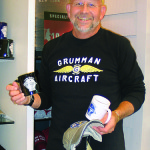 Ted Kole poses with the merchandise he designs and sells to commemorate the corporation.