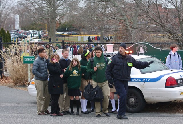 A Riverhead police officer guides students at Mercy following a bomb threat Wednesday. (Credit: Barbaraellen Koch)