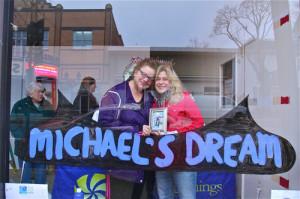BARBARAELLEN KOCH PHOTO | Nancy Reyer, left, and Allison Pressler, right, at a window display made to recognize Reyer's son, Michael.
