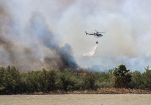 A helicopter drops fire suppression on the Topock/Pirate Fire Wednesday morning. Rick Powell/RiverScene