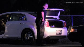 An officer checks the trunk of the Monte Carlo that fled from Hemet PD officers.