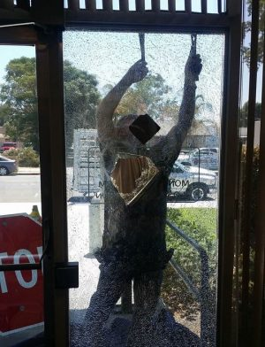 A glass worker begins to remove the shattered window. Ricardo Ruelas photo