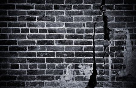 10289619-a-dark-and-grungy-brick-wall-with-cracks-and-damage-done-in-black-and-white