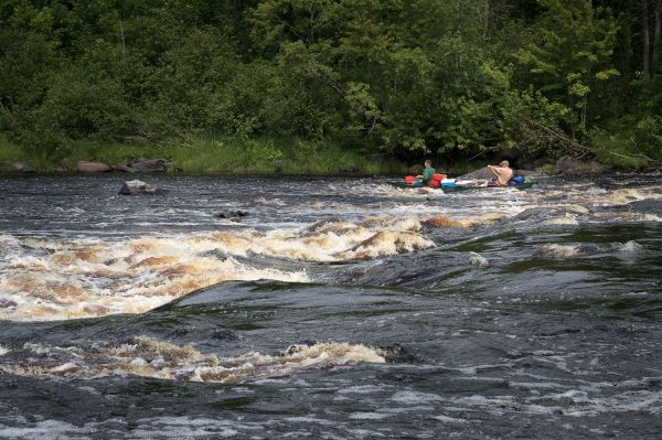 """Here we watch as a flat-bottomed Royalex canoe bounces awkwardly---yet successfully---through Beaver Dam Rapids."""