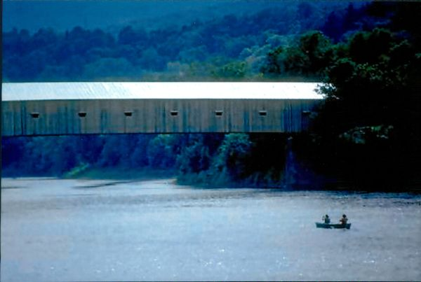 Canoeing beneath a covered bridge.