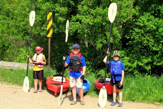 kids posing in front of kayaks for Mothers Day kayaking adventure