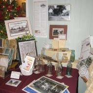 A display includes photos and artifacts from various business enterprises and a vertical wall banner which outlines the history of the New Leaf building.